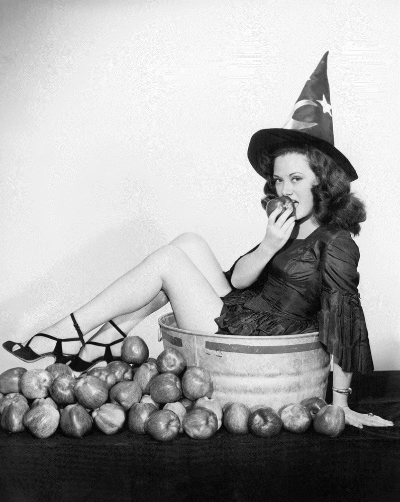 Girl in bucket with apples for halloween