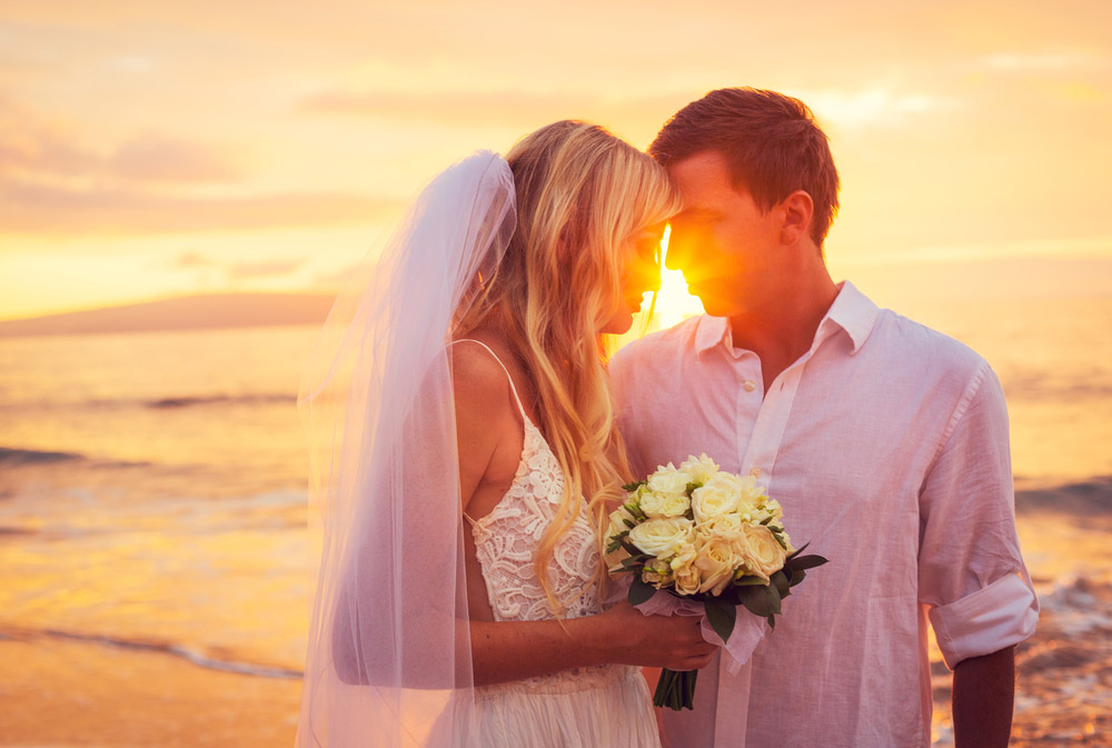 Couple kissing on beach in golden hour