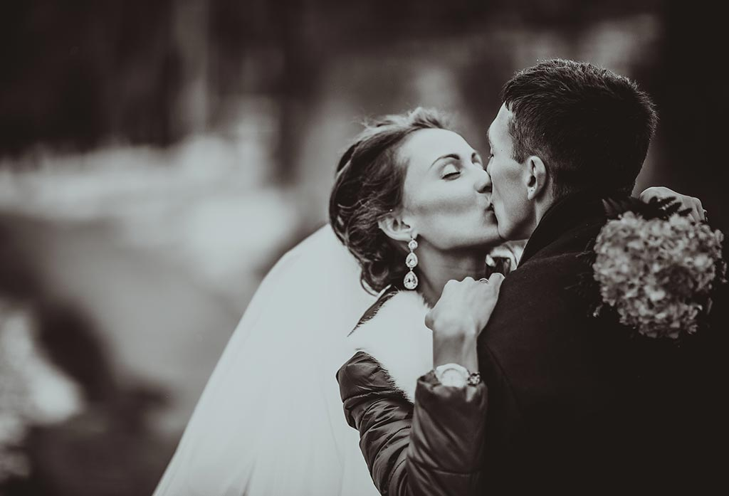 Black and white photo of married couple kissing